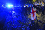 An English fan draped in a flag walks through litter and broken glass in Trafalgar Square, London during the UEFA Euro 2020 Final between Italy and England, Sunday July 11, 2021. (Victoria Jones/PA Via AP)