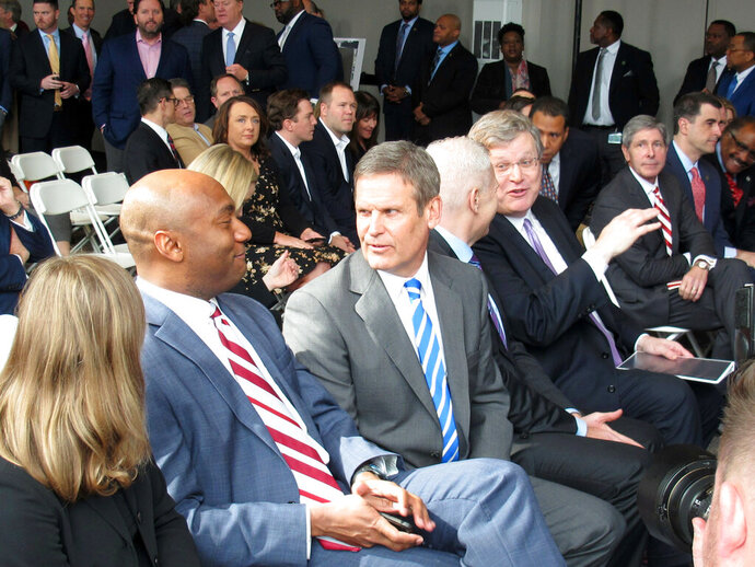 Shelby County Mayor Lee Harris, second from left, speaks with Tennessee Gov. Bill Lee during an announcement by FedEx Logistics that it is establishing its headquarters in a downtown Memphis building on Tuesday, Feb. 12, 2019, in Memphis, Tenn. (AP Photos/Adrian Sainz)