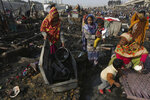 Dwellers collect their belongings after a fire gutted their homes in Karachi, Pakistan, Wednesday, Jan. 22, 2020. Hundreds of huts were burnt to ashes as fire erupted making dozens of families homeless in a slum of Karachi, local media reported. (AP Photo/Fareed Khan)