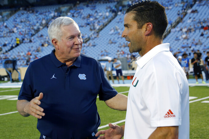 North Carolina coach Mack Brown, left, and Miami coach Manny Diaz chat before an NCAA college football game in Chapel Hill, N.C., Saturday, Sept. 7, 2019. (AP Photo/Chris Seward)