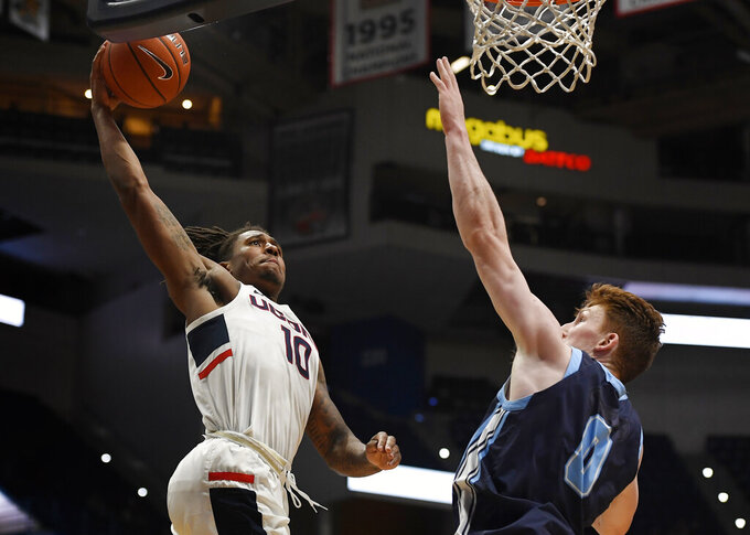 Connecticut's Brendan Adams, left, lines up a dunk as Maine's Andrew Fleming, right, defends during the second half of an NCAA college basketball game, Sunday, Dec. 1, 2019, in Hartford, Conn. (AP Photo/Jessica Hill)