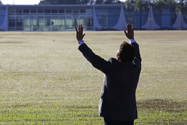 An evangelical pastor prays for Brazil's President Jair Bolsonaro, who said he tested positive for COVID-19, outside Alvorada Palace, the president's official residence in Brasilia, Brazil, Tuesday, July 7, 2020. (AP Photo/Eraldo Peres)