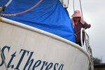 Tuyet Tran ties down a tarp on her shrimp boat in Morgan City, La. Monday, May 11, 2020. Attempts to curb the spread of COVID-19 have visited a kind of triple economic whammy on the state. As oil prices have plummeted, the industry laid off workers. Tourism has dried up, meaning more lost jobs. And one major tourist draw — cuisine built around fin fish, shrimp, oyster and crabs — is also suffering. (AP Photo/Gerald Herbert)