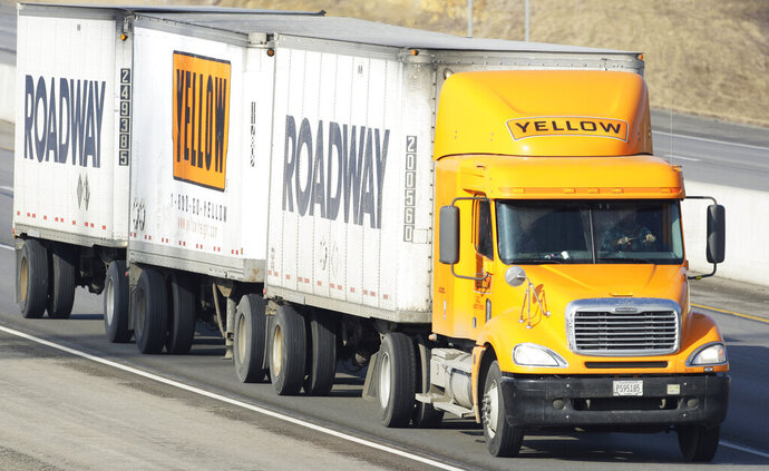 """FILE - In this Feb. 2, 2010, file photo, a Yellow Freight/Roadway Express truck travels east on I-70, near Lecompton, Kan. The struggling trucking company once sued by the Department of Defense is getting a $700 million loan from the U.S. government because it is """"critical to maintaining national security,"""" the Treasury Department said Wednesday, July 1, 2020. U.S. taxpayers will take a 29.6% stake in YRC Worldwide as a result of the deal, which was made as part of the Coronavirus Aid, Relief, and Economic Security Act. (AP Photo/Orlin Wagner, File)"""