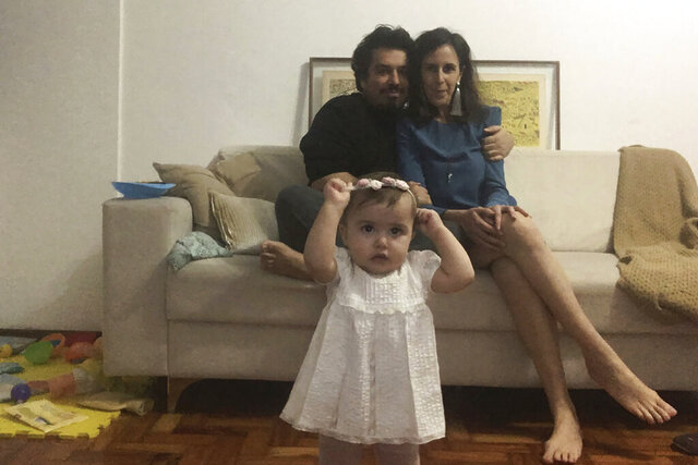 In this May 29, 2020, photo, Associated Press writer Mauricio Savarese sits with his partner Luisa Belchior as their daughter Carolina, 1, looks on in their home in Sao Paulo. Savarese and Belchior paid for the visit of a notary officer to get their civil union certificate, like many Brazilians that want to avoid bigger risk of contracting COVID-19. (AP Photo/Mauricio Savarese)
