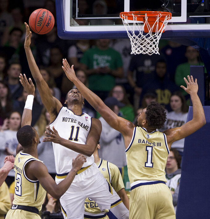Notre Dame's Juwan Durham (11) goes up for a shot between Georgia Tech's Curtis Haywood II, left, and James Banks III (1) during the first half of an NCAA college basketball game Sunday, Feb. 10, 2019, in South Bend, Ind. (AP Photo/Robert Franklin)
