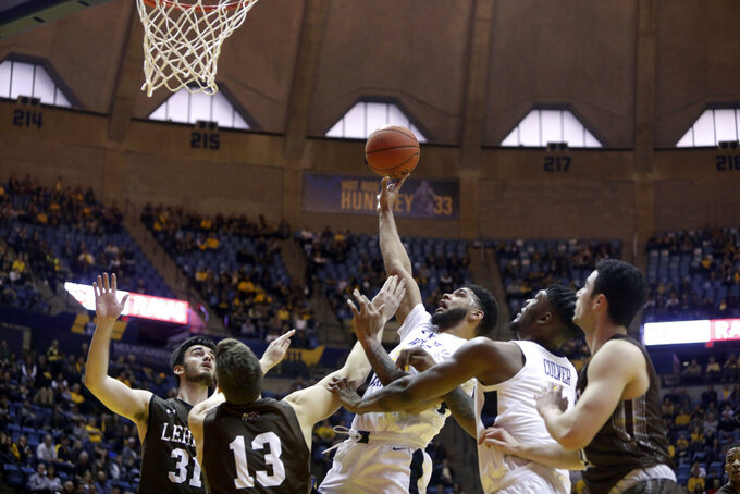 West Virginia forward Esa Ahmad (23) shoots while defended by Lehigh center James Karnik (13) during the second half of an NCAA college basketball game Sunday, Dec. 30, 2018, in Morgantown, W.Va. (AP Photo/Raymond Thompson)
