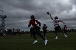 Houston Texans' center Nick Martin, 66, tries to catch a ball from quarterback Deshaun Watson, 4, during an NFL practice session at the London Irish rugby team training ground in the Sunbury-on-Thames suburb of south west London, Friday, Nov. 1, 2019. The Houston Texans are preparing for an NFL regular season game against the Jacksonville Jaguars in London on Sunday. (AP Photo/Matt Dunham)