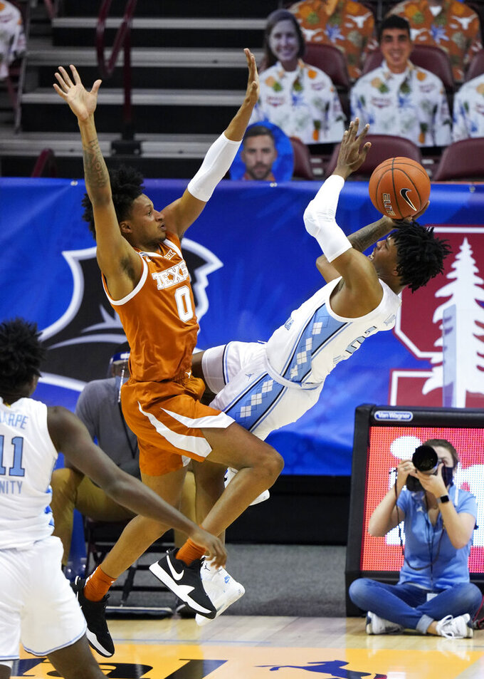 North Carolina guard Caleb Love (2) falls backwards as his shot at the basket is blocked by Texas forward Gerald Liddell (0) in the first half of an NCAA college basketball game for the championship of the Maui Invitational, Wednesday, Dec. 2, 2020, in Asheville, N.C. Texas won 69-67. (AP Photo/Kathy Kmonicek)