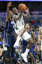 Milwaukee Bucks' Eric Bledsoe (6) goes to the basket in front of Orlando Magic's Al-Farouq Aminu (2) during the second half of an NBA basketball game Friday, Nov. 1, 2019, in Orlando, Fla. (AP Photo/John Raoux)