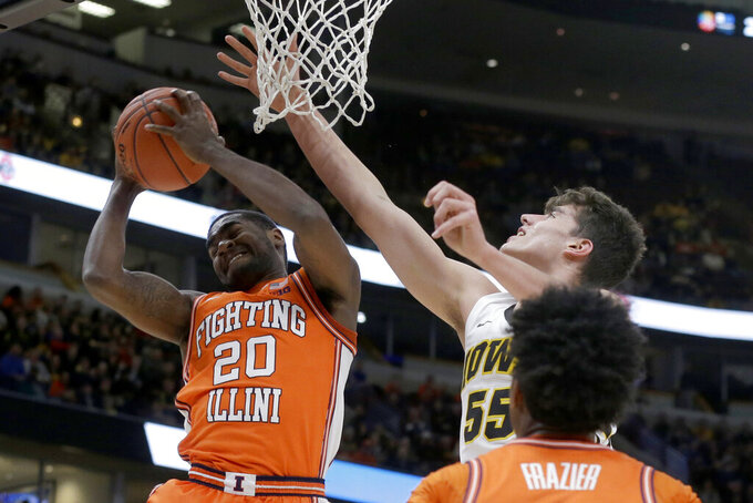 Illinois's Da'Monte Williams (20) grabs a rebound against Iowa's Luka Garza (55) during the first half of an NCAA college basketball game in the second round of the Big Ten Conference tournament, Thursday, March 14, 2019, in Chicago. (AP Photo/Kiichiro Sato)