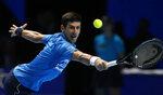 Serbia's Novak Djokovic plays a return to Austria's Dominic Thiem during their ATP World Tour Finals singles tennis match at the O2 Arena in London, Tuesday, Nov. 12, 2019. (AP Photo/Alastair Grant)