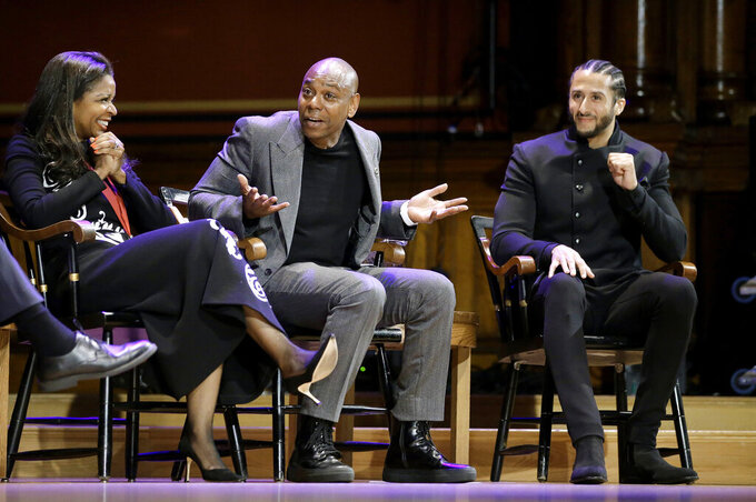 FILE - In this Oct. 11, 2018, file photo, comedian Dave Chappelle, center, shares a light moment with philanthropist Pamela Joyner, left, and former NFL quarterback Colin Kaepernick, right, on stage during W.E.B. Du Bois Medal award ceremonies at Harvard University in Cambridge, Mass. When George Floyd died under the knee of a Minneapolis policeman, Harvard basketball coach Tommy Amaker knew it was time to get to work. Amaker brings players to the annual W.E.B. Du Bois Award ceremony, where Harvard honors trailblazers in politics, culture and business. Among them are Chappelle and Kaepernick. (AP Photo/Steven Senne, File)