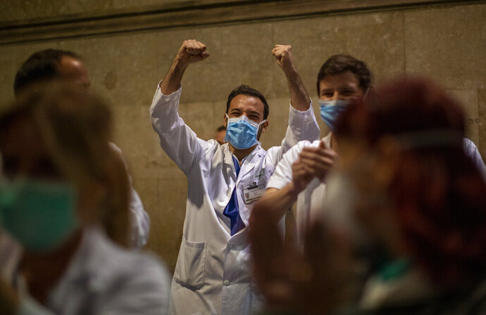 Health workers react as people applaud from their houses in support of the medical staff that are working on the COVID-19 virus outbreak at the main gate of the Hospital Clinic in Barcelona, Spain, Thursday, March 26, 2020. The new coronavirus causes mild or moderate symptoms for most people, but for some, especially older adults and people with existing health problems, it can cause more severe illness or death. (AP Photo/Emilio Morenatti)