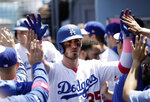 Los Angeles Dodgers' Cody Bellinger gets high-fives in the dugout after scoring on a sacrifice fly ball from Corey Seager during the second inning of a baseball game against the Washington Nationals, Sunday, May 12, 2019, in Los Angeles. (AP Photo/Marcio Jose Sanchez)
