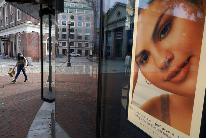 FILE - A woman carries a shopping bag while walking past a cosmetics store, right, near Faneuil Hall, behind left, Monday, Sept. 28, 2020, in Boston. The U.S. economy expanded at a 33.4% annual pace from July through September, the Commerce Department said Tuesday, Dec. 22, 2020 delivering the last of three estimates on the economy's third-quarter performance.  (AP Photo/Steven Senne, file)