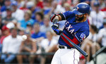 Texas Rangers' Nomar Mazara makes contact for a sacrifice fly during the third inning of a baseball game against the Houston Astros, Saturday, July 13, 2019, in Arlington, Texas. Shin-Soo Choo and Danny Santana scored on a throwing error by Astros center fielder George Springer. (AP Photo/Brandon Wade)