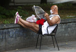 A man reads a newspaper siting in a street in Skopje, North Macedonia on Thursday, July 16, 2020, a day after the country's parliamentary elections. The pro-Western SDSM party in North Macedonia is poised to try to form a coalition government following a narrow election victory. (AP Photo/Boris Grdanoski)