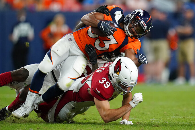 Arizona Cardinals defensive back Tyler Sigler (39) trips up Denver Broncos running back Khalfani Muhammad (33) during the second half of an NFL preseason football game, Thursday, Aug. 29, 2019, in Denver. (AP Photo/Jack Dempsey)