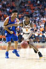 Oklahoma State guard Avery Anderson III (0) drives past Kansas guard Devon Dotson (1) during the first half of an NCAA college basketball game in Stillwater, Okla., Monday, Jan. 27, 2020. (AP Photo/Brody Schmidt)
