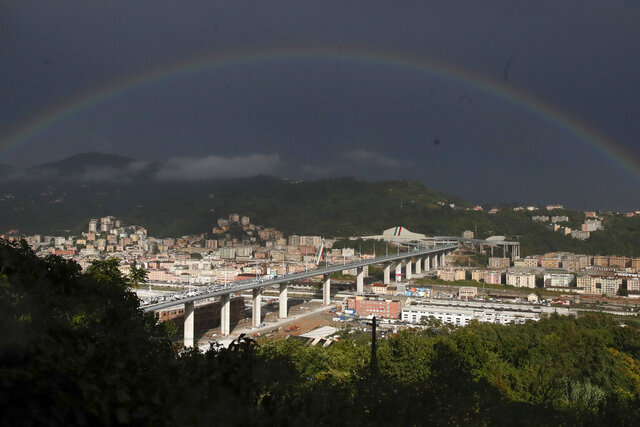 A rainbow shines over the new San Giorgio Bridge in Genoa, Italy, Monday, Aug. 3, 2020. Two years ago this month, a stretch of roadbed collapsed on Genoa's Morandi Bridge, sending cars and trucks plunging to dry riverbed below and ending 43 lives. On Monday, Italy's president journeys to Genoa for a ceremony to inaugurate a replacement bridge. (AP Photo/Antonio Calanni)