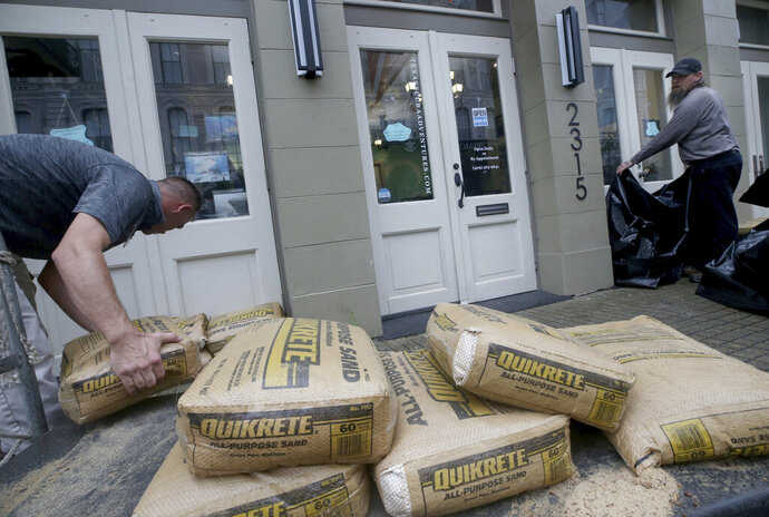 Jeremy Franklin, left, with Mitchell Historic Properties, unloads bags of sand at Texas Scuba Adventures, in Galveston, Texas as he and Chad Sterns prepare for possible flooding from Tropical Storm Imelda on Tuesday, Sept. 17, 2019. (Jennifer Reynolds/The Galveston County Daily News via AP)
