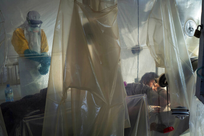 File-In this July 13, 2019 file photo, health workers wearing protective gear check on a patient isolated in a plastic cube at an Ebola treatment center in Beni, Congo. Health authorities in Congo have halted an Ebola treatment study early with good news: Two of the four experimental drugs seem to be saving lives. More than 1,800 people have died in the African country's yearlong outbreak.  (AP Photo/Jerome Delay, File)
