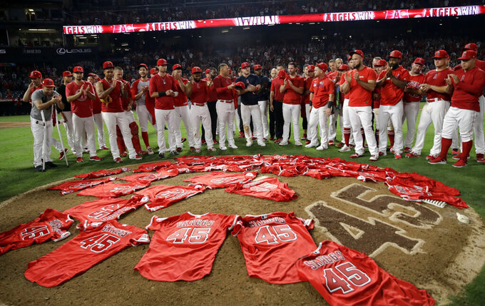 Members of the Los Angeles Angels place their jerseys with No. 45 in honor of pitcher Tyler Skaggs on the mound after a combined no-hitter against the Seattle Mariners during a baseball game, July 12, 2019, in Anaheim, Calif. (AP Photo/Marcio Jose Sanchez)