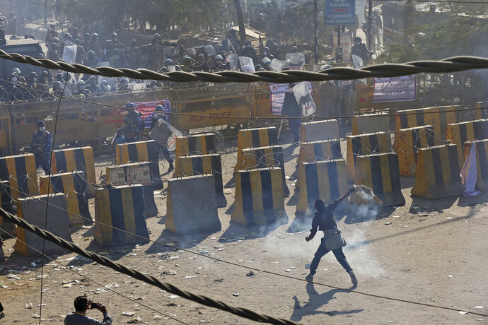 A farmer throws back a tear gas shells towards policemen, at the border between Delhi and Haryana state, Friday, Nov. 27, 2020. Thousands of agitating farmers in India faced tear gas and baton charge from police on Friday after they resumed their march to the capital against new farming laws that they fear will give more power to corporations and reduce their earnings. While trying to march towards New Delhi, the farmers, using their tractors, cleared concrete blockades, walls of shipping containers and horizontally parked trucks after police had set them up as barricades and dug trenches on highways to block roads leading to the capital. (AP Photo/Altaf Qadri)