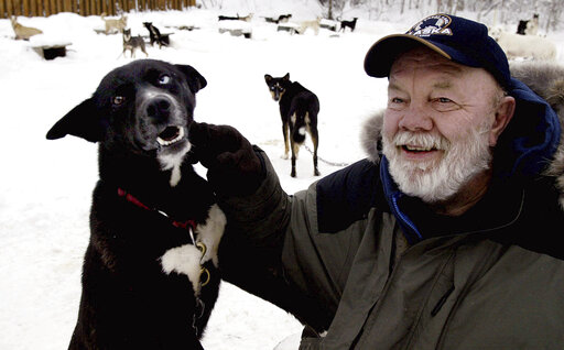 FILE - Author Gary Paulsen sits with his favorite Alaskan husky, Flax, at his Willow, Alaska, home on Feb. 10, 2005. Paulsen died Wednesday, Oct. 13, 2021 at age 82. (AP Photo/Al Grillo, File)