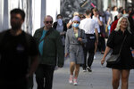 Shoppers wear masks on Oxford Street in London, Monday, Sept. 21, 2020. Britain's top medical advisers have painted a grim picture of exponential growth in illness and death if nothing is done to control the second wave of coronavirus infections, laying the groundwork for the government to announce new restrictions later this week.(AP Photo/Kirsty Wigglesworth)