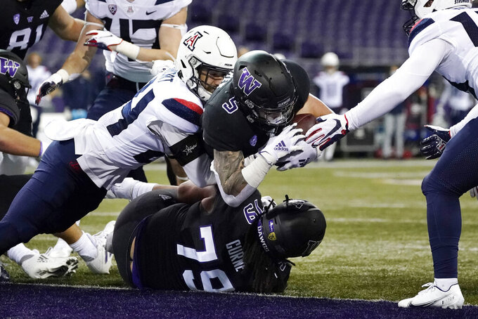 Washington's Sean McGrew (5) dives over teammate Victor Curne (79) to score against Arizona during the first half of an NCAA college football game Saturday, Nov. 21, 2020, in Seattle. (AP Photo/Elaine Thompson)