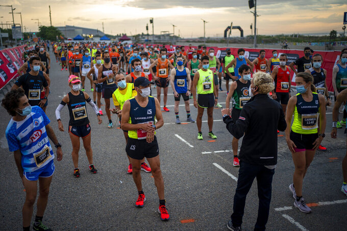 """Athletes wearing face masks to prevent the spread of coronavirus keep their positions before taking part in """"La Cursa de la Mercè"""" race, one of the most emblematic events of Barcelona's sporting calendar, Spain, Saturday, Sept. 19, 2020. The race """"La Cursa de la Mercè"""" runs across 10km in Barcelona city and this year is dedicated to the fight against COVID-19. (AP Photo/Emilio Morenatti)"""