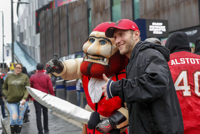 An NFL football fan poses for a photo with Tampa Bay Buccaneers mascot Captain Fear outside Tottenham Hotspur Stadium to watch an NFL football game between the Tampa Bay Buccaneers and the Carolina Panthers, Sunday, Oct. 13, 2019, in London. (AP Photo/Alastair Grant)