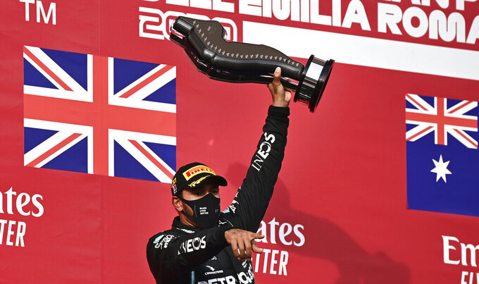 Mercedes driver Lewis Hamilton of Britain holds up the trophy on the podium after winning the Emilia Romagna Formula One Grand Prix, at the Enzo and Dino Ferrari racetrack, in Imola, Italy, Sunday, Nov.1, 2020. (Miguel Medina, Pool via AP)