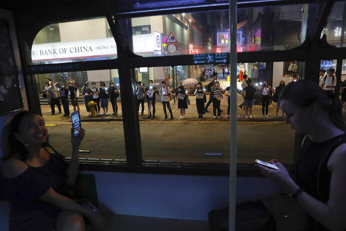 Demonstrators, seen from inside a tram, link hands along a street in Hong Kong, Friday, Aug. 23, 2019. Supporters of Hong Kong's pro-democracy movement created human chains on both sides of the city's harbor Friday, inspired by a historic protest 30 years ago in the Baltic states against Soviet control. (AP Photo/Kin Cheung)