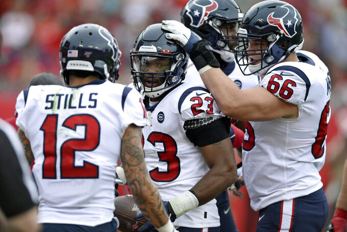 Houston Texans running back Carlos Hyde (23) celebrates with wide receiver Kenny Stills (12) and center Nick Martin (66) after his 1-yard touchdown run against the Tampa Bay Buccaneers during the first half of an NFL football game Saturday, Dec. 21, 2019, in Tampa, Fla. (AP Photo/Jason Behnken)