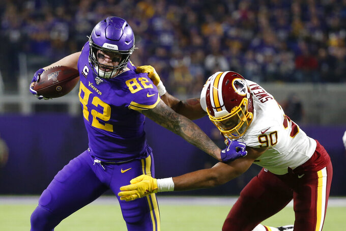 Minnesota Vikings tight end Kyle Rudolph (82) runs from Washington Redskins linebacker Montez Sweat, right, after catching a pass during the second half of an NFL football game, Thursday, Oct. 24, 2019, in Minneapolis. (AP Photo/Bruce Kluckhohn)
