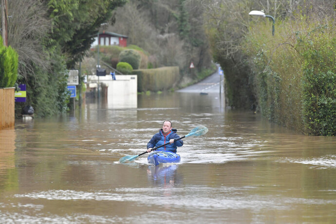 A man travels by boat through floodwater in Monmouth, Wales, Tuesday Feb. 18, 2020. Britain's Environment Agency issued severe flood warnings Monday, advising of life-threatening danger after Storm Dennis dumped weeks' worth of rain in some places. (Ben Birchall/PA via AP)