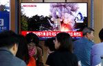People watch a TV showing a file image of North Korea's missile launch during a news program at the Seoul Railway Station in Seoul, South Korea, Wednesday, Oct. 2, 2019. North Korea on Wednesday fired projectiles toward its eastern sea, South Korea's military said, in an apparent display of its expanding military capabilities ahead of planned nuclear negotiations with the United States this weekend. (AP Photo/Ahn Young-joon)