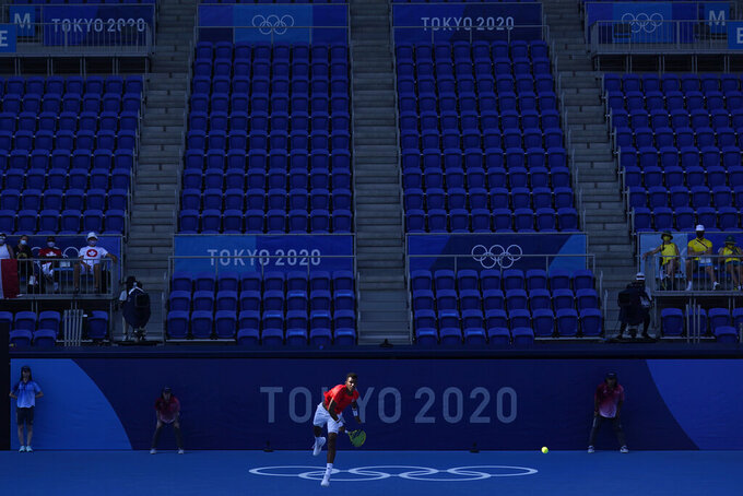 FILE - In this July 25, 2021, file photo, Felix Auger-Aliassime, of Canada, plays against Max Purcell, of Australia, during the first round of the tennis competition at the 2020 Summer Olympics in Tokyo, Japan. In arenas across Tokyo, athletes accustomed to feeding off the deafening roar of the crowd are searching for new ways to feel Olympic enthusiasm. (AP Photo/Seth Wenig, File)