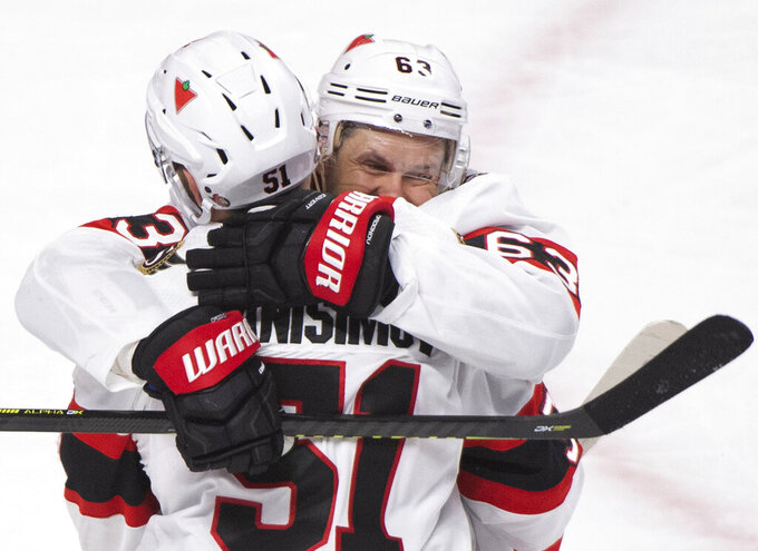 Ottawa Senators' Evgenii Dadonov (63) celebrates with Artem Anisimov after scoring against the Montreal Canadiens during the second period of an NHL hockey game in Montreal, Saturday, April 3, 2021. (Graham Hughes/The Canadian Press via AP)