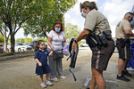 Miami-Dade County Police officer Gina Hogen, right, gives a book bag and school supplies to Haley Hernandez, left, 3, and her grandmother Alicia Hernandez during a book bag give away at the office of county commissioner Joe Martinez, Friday, July 30, 2021, in Miami. (AP Photo/Wilfredo Lee)