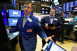 Specialist Thomas Schreck, left, works with traders on the floor of the New York Stock Exchange, Monday, Nov. 4, 2019. Stocks are opening higher on Wall Street, pushing major indexes toward more record highs. (AP Photo/Richard Drew)