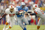 FILE - In this Nov. 10, 1991, file photo, Detroit Lions running back Barry Sanders, center, plows his way through two defenders during an NFL football game against the Tampa Bay Buccaneers in Tampa, Fla. The Lions have drafted some all-time NFL greats such as Hall of Fame running back Sanders. (AP Photo/Chris O'Meara, File)