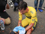 Slovenia's Primoz Roglic sits on the road after losing the overall leader's yellow jersey in stage 20 of the Tour de France cycling race, an individual time trial over 36.2 kilometers (22.5 miles), from Lure to La Planche des Belles Filles, France, Saturday, Sept. 19, 2020. (Christophe Petit-Tesson/Pool via AP)