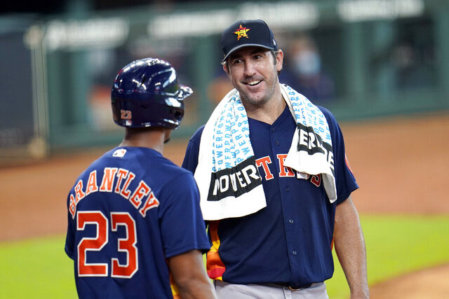Houston Astros pitcher Justin Verlander, right, talks with Michael Brantley (23) after throwing during a simulated baseball game Thursday, July 9, 2020, in Houston. (AP Photo/David J. Phillip)