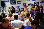 Former Vice President and Democratic presidential candidate Joe Biden, center, makes a call during a campaign phone bank event an electrical workers union hall Saturday, July 20, 2019, in Las Vegas. (AP Photo/John Locher)