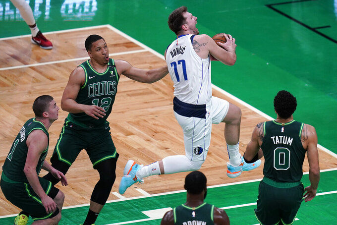 Dallas Mavericks guard Luka Doncic (77) drives through the Boston Celtics's defense during the first half of an NBA basketball game Wednesday, March 31, 2021, in Boston. (AP Photo/Charles Krupa)