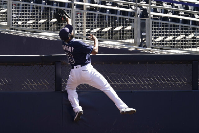 Tampa Bay Rays right fielder Manuel Margot reaches over a right field wall after catching a foul ball by Houston Astros center fielder George Springer during the second inning in Game 2 of a baseball American League Championship Series, Monday, Oct. 12, 2020, in San Diego. (AP Photo/Jae C. Hong)